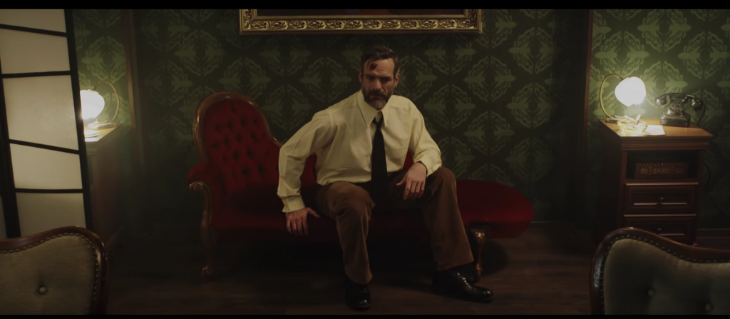 Un homme est assis dans une pièce vieillote.