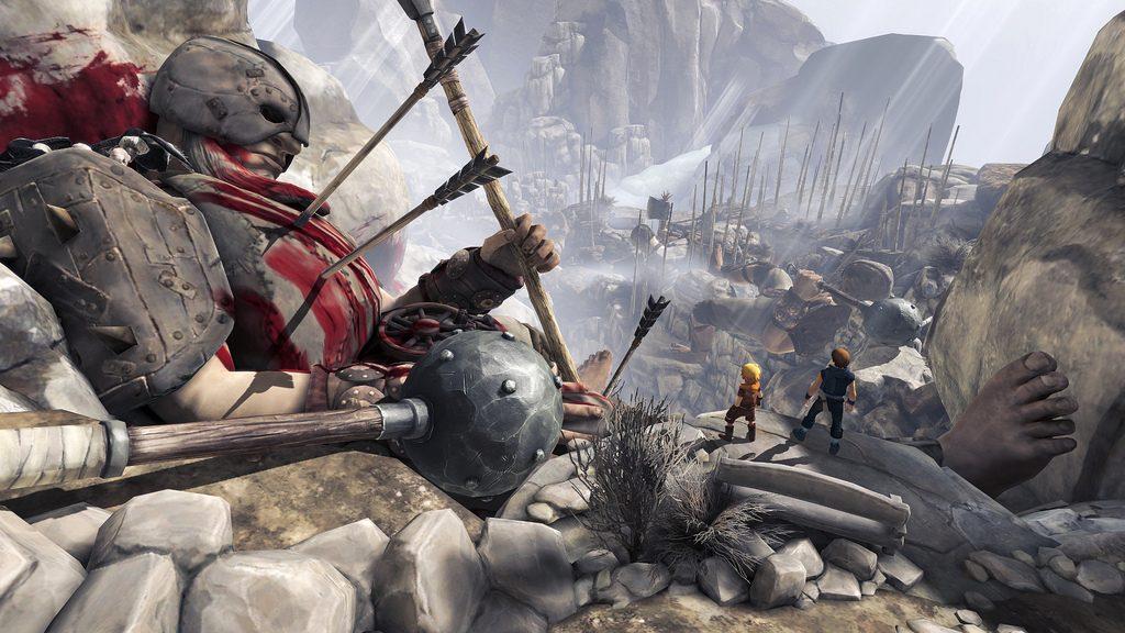 Les frères se tiennent devant un gouffre dans les montagnes qui contient le reste d'une bataille. A gauche, un cadavre de geant criblé de flèches les surplombe.